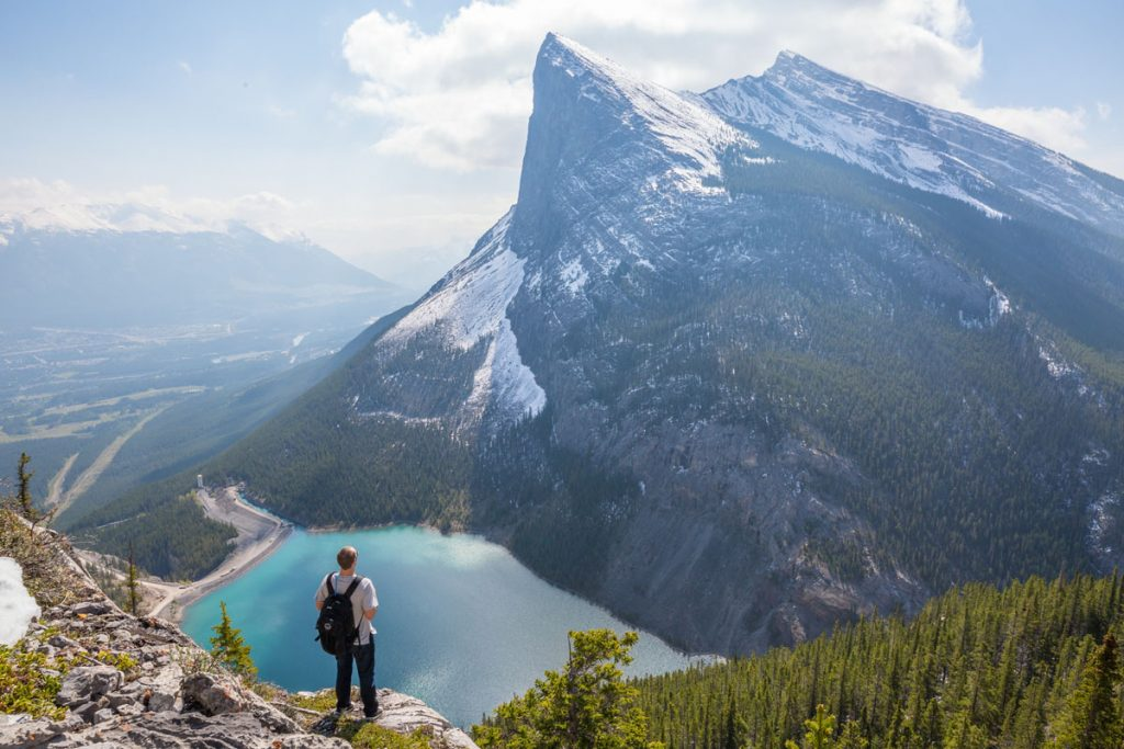 guy hiking and looking over a lake