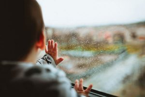 Kid touching and looking out a rainy window