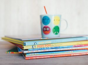 A stack of childrens' books and a colourful cup