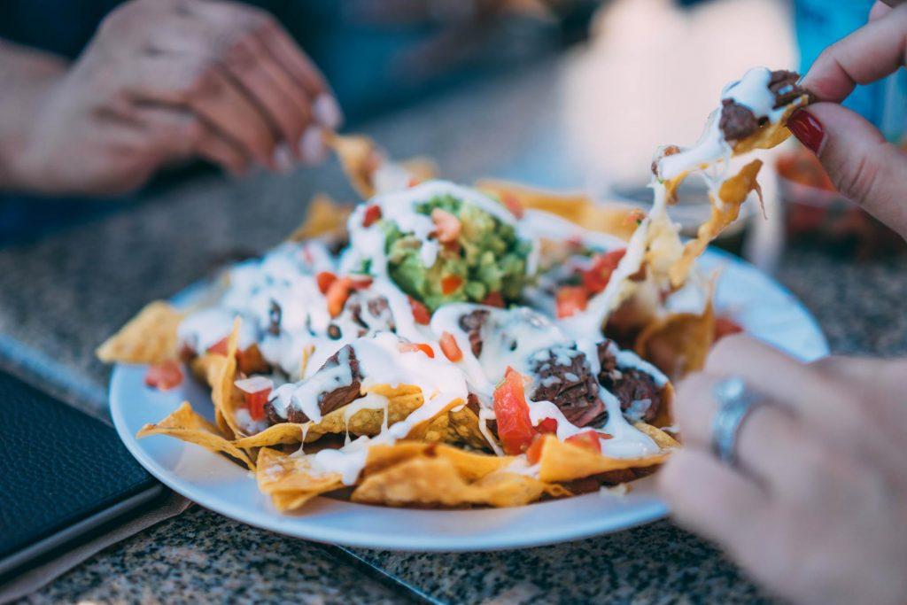 A plate of greek yogurt tortilla chips being shared