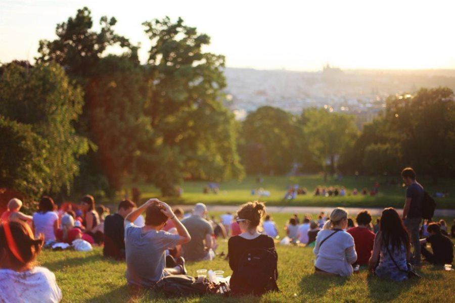 people sitting in a park enjoying free music