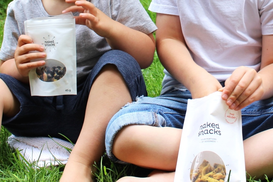 two kids eating bags of 3pm goji and thai holiday snack mixes from naked snacks