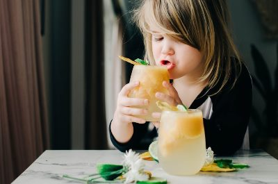 Girl sipping a glass of sparkly mango slushy about to spill