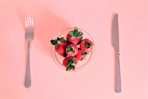 plate of strawberries on a pink background