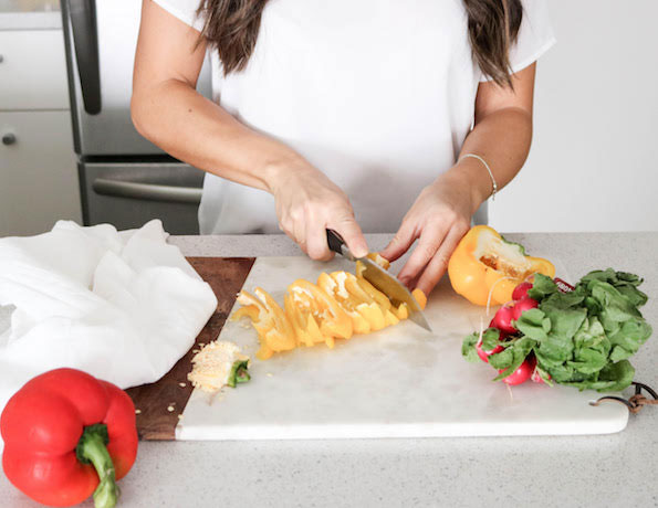 woman cutting yellow bell peppers on a cutting board with the seeds taken out