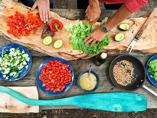 people preparing a salad spread