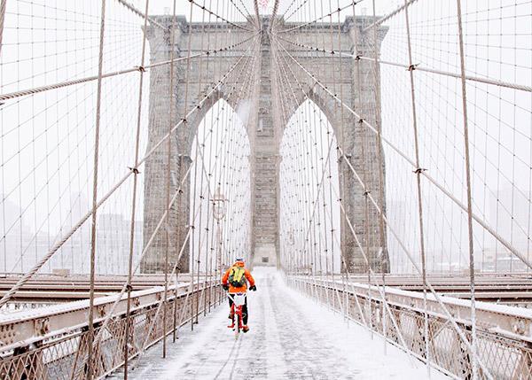 biker crossing a bridge