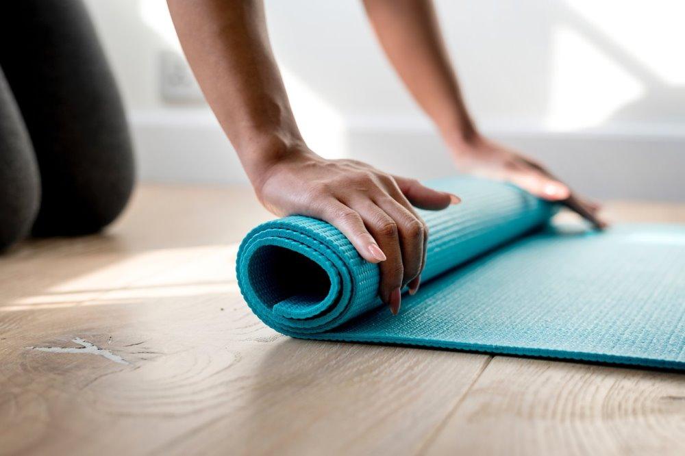 woman rolling up a blue yoga mat