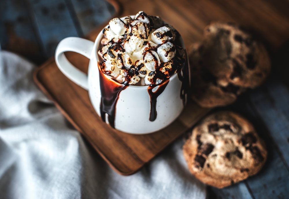 Hot chocolate in a mug with roasted marshmallows on top and chocolate syrup dripping out, and cookies on the side