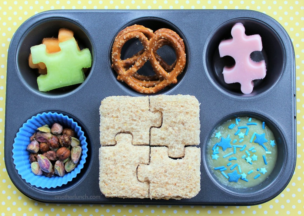 Cute snacks with puzzle shaped fruits, pretzels, pistachio nuts, and cookies in a muffin tin
