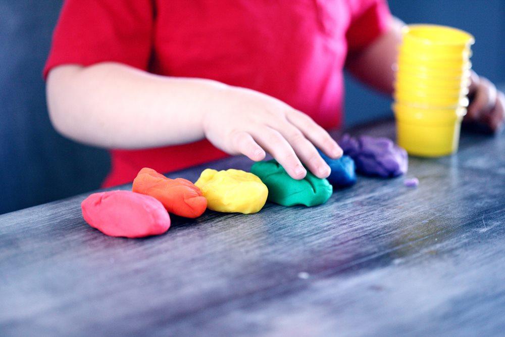 Kid playing with rainbow coloured playdough