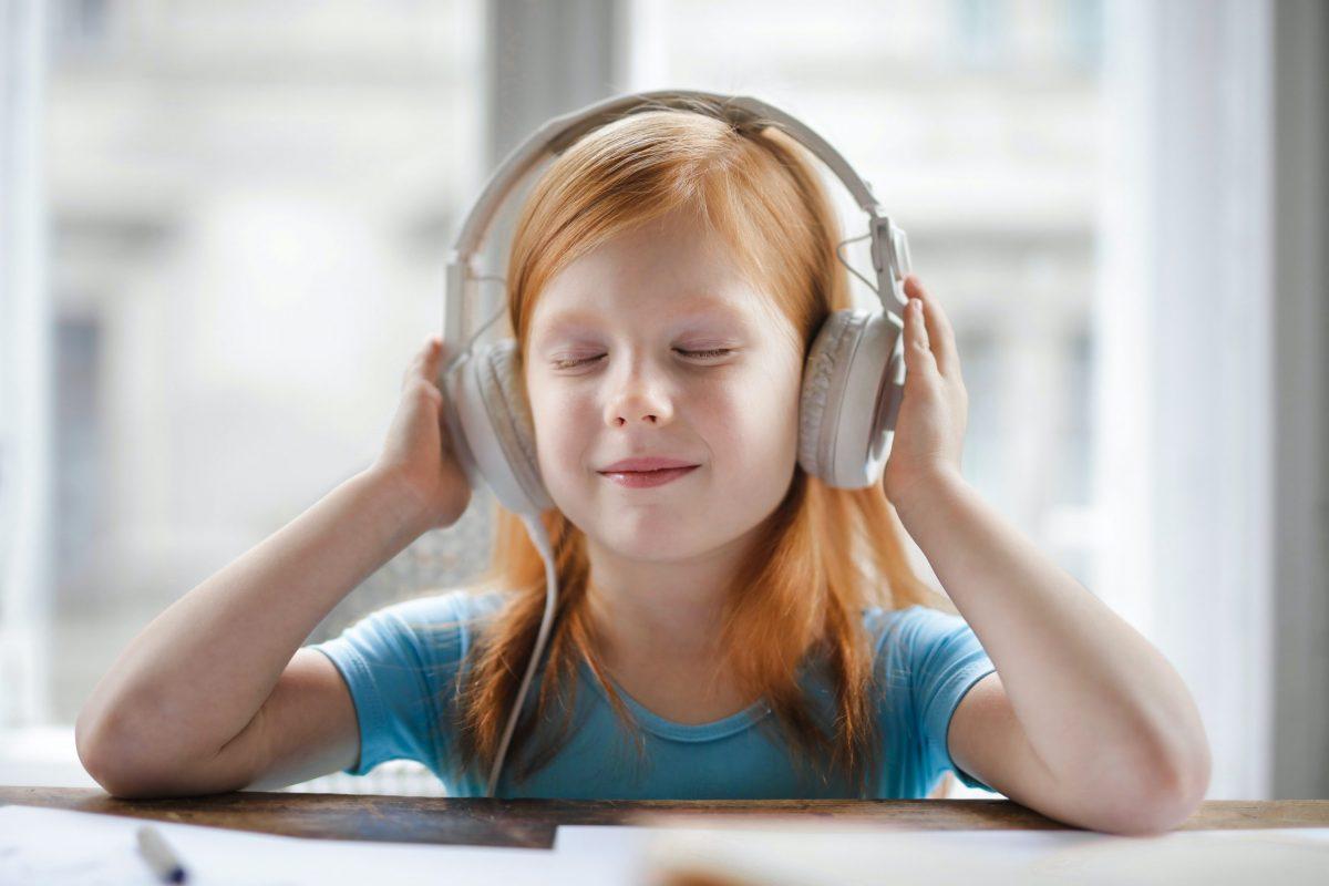 little red hair girl listening to music on headphones