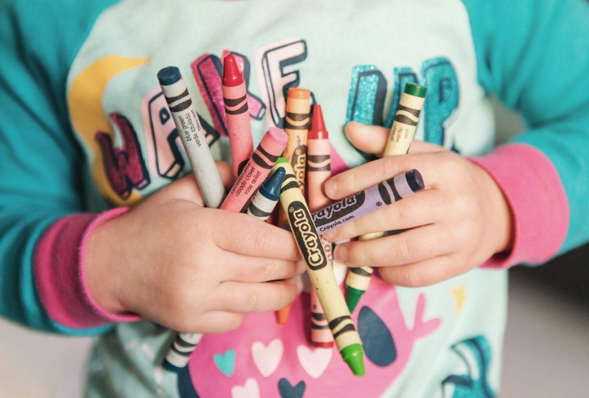 child holding crayola crayons