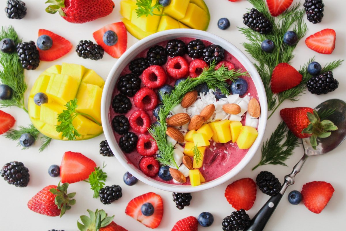 A yoghurt bowl with raspberries, blackberries, mangoes, coconut, blueberries and almonds surrounded by fruit