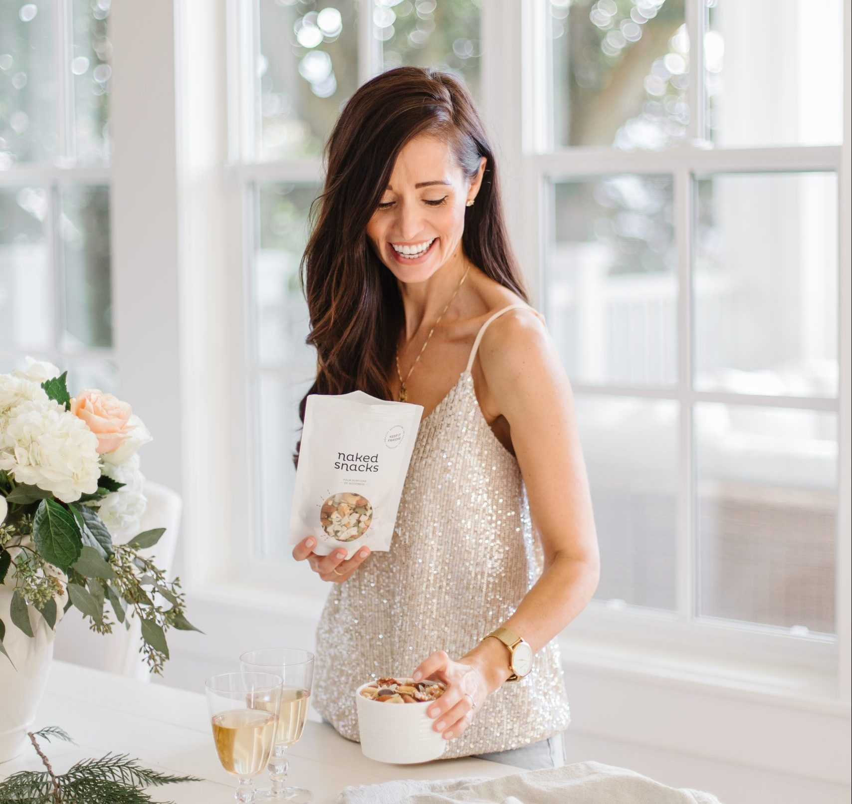 Tori Wessner holding a bag of Keep it Fraiche Snack, in a bright kitchen