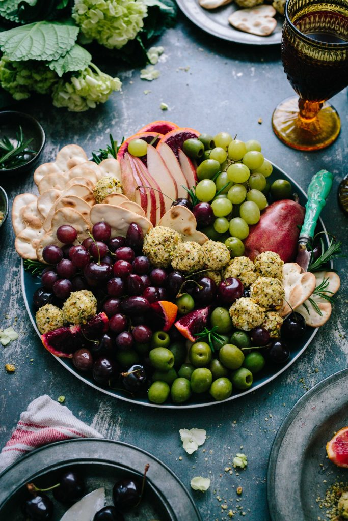 a holiday plate of fruits and high-fibre foods, with grapes, olives, crackers,  apples