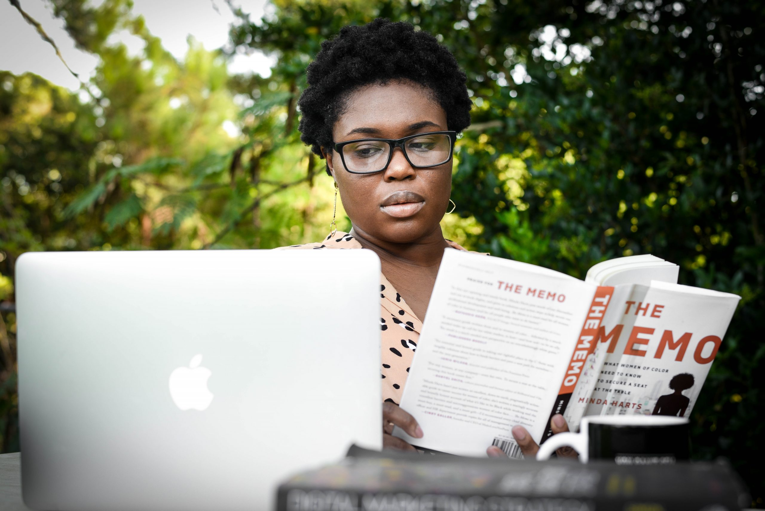 Woman in glasses reading the book by the laptop