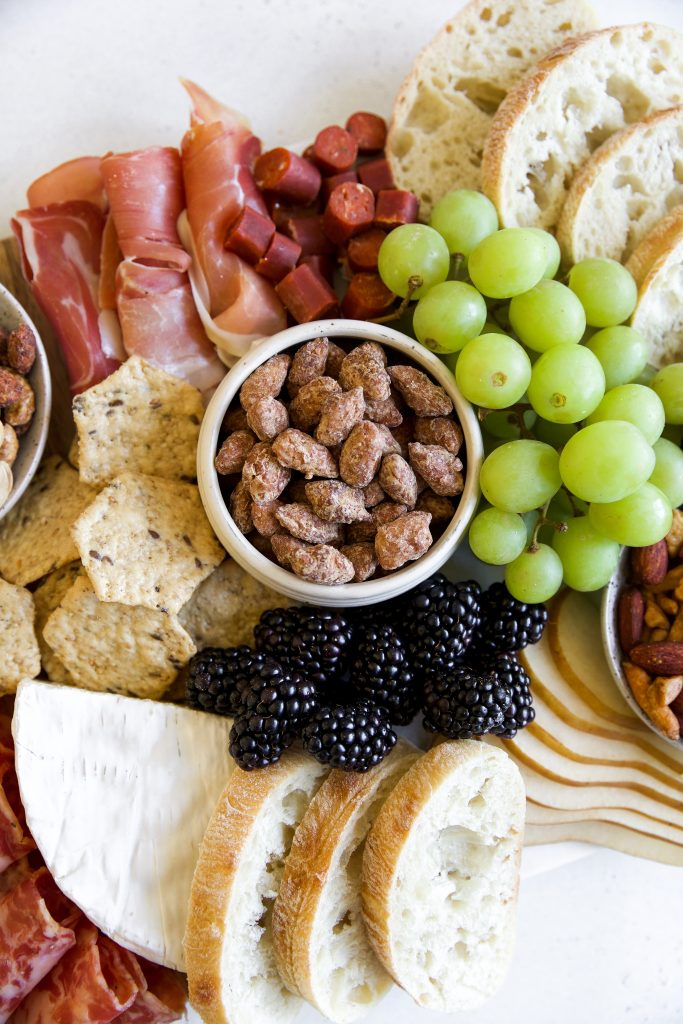 charcuterie board with fresh grapes, curated meats and Laid Back Snacks Maple Praline Almonds