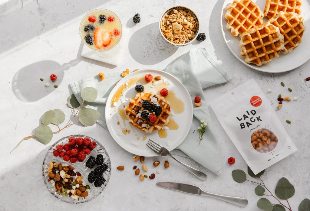 Laid Back Snacks Hearty Tamari laying on white table with berry waffles, a tray of snacks and berries and mimosa