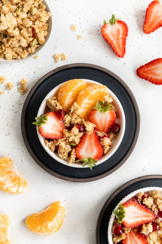 Parfait bowl with granola, oranges and strawberries in a white bowl.