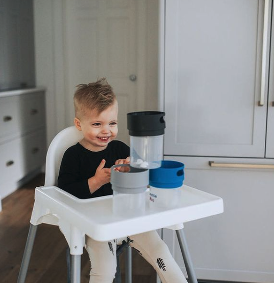 a child looking at Munchie Mug spill-proof snack cups