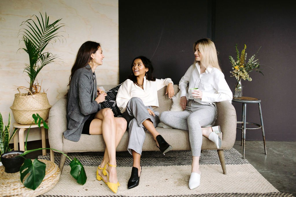 Three women sitting next to each other wearing Leze the Label